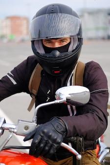 Rowerzysta mężczyzna lub facet-kierowca w kasku siedzi na motocyklu.