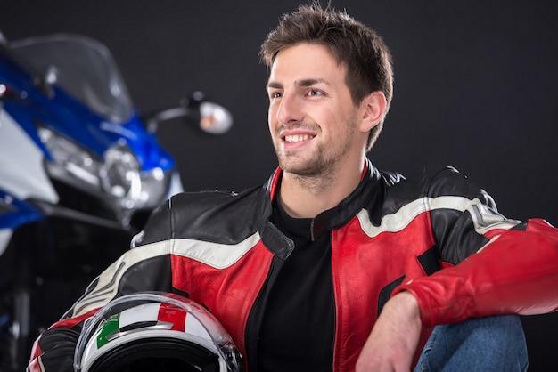 Rowerzysta mężczyzna ono uśmiecha się z motocyklem