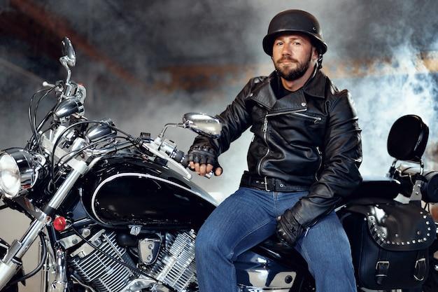 Rowerzysta mężczyzna w skórzanej kurtce i kasku siedzi na swoim motocyklu