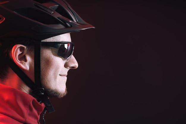 Rowerzysta. młody człowiek w kasku na rowerze