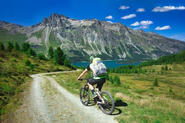Rowerzysta na górskiej polnej drodze w pięknym krajobrazie gór