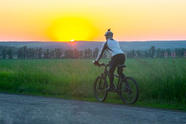 Rowerzysta na rowerze jeździ po polach pszenicy w słońcu. sporty i hobby. zajęcia na świeżym powietrzu