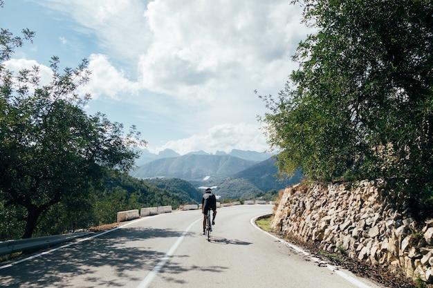 Rowerzysta na rowerze o zachodzie słońca w górskiej drodze