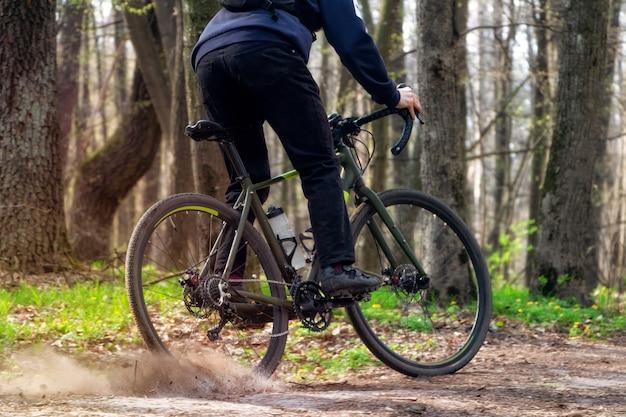 Rowerzysta na rowerze szutrowym. rowerzysta jedzie leśną ścieżką, dryfując tylnym kołem i podnosząc boisko.