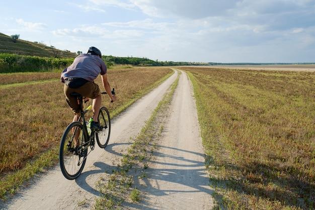 Rowerzysta na rowerze w kasku jeździć dużą prędkością, widok z tyłu
