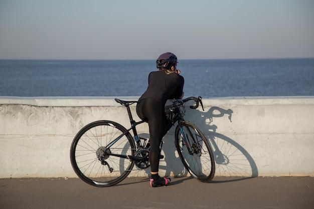 Rowerzysta odpoczywa na nasypie, spoglądając w stronę wody