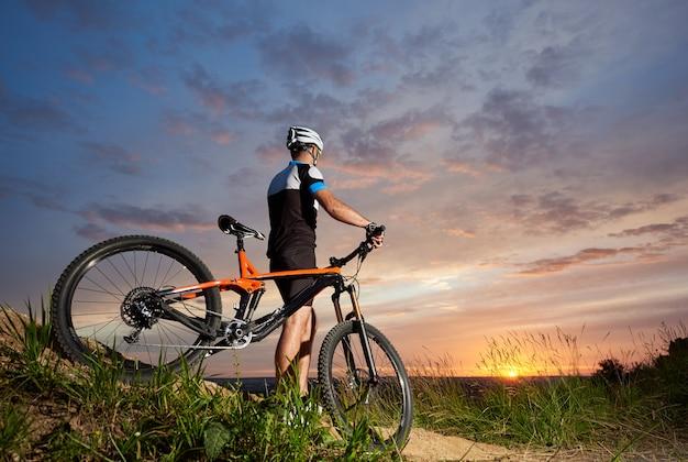 Rowerzysta odpoczywa o zachodzie słońca