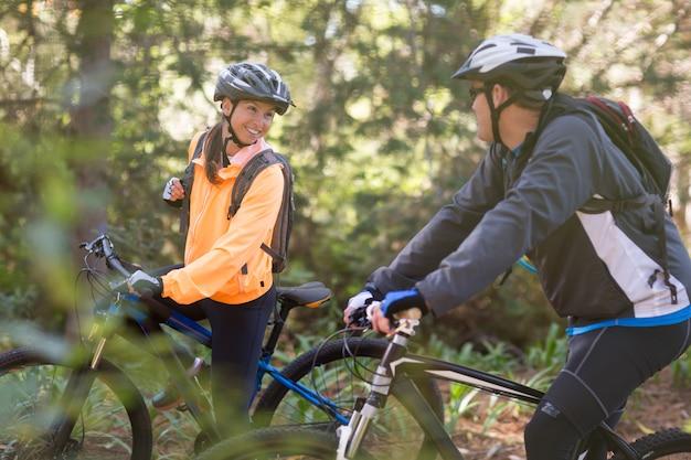 Rowerzysta para jedzie rower górski w lesie