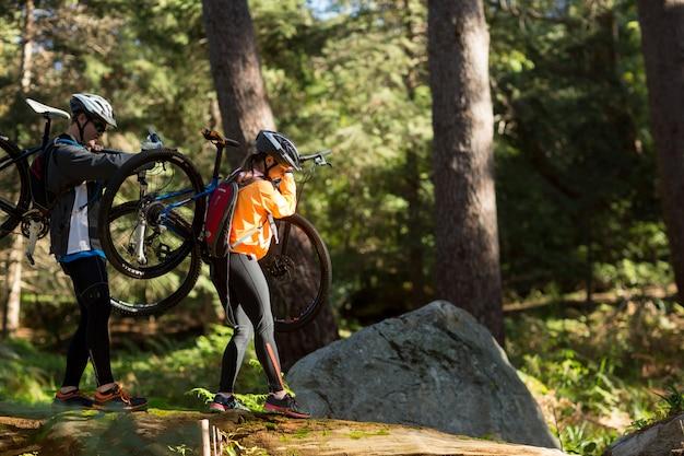 Rowerzysta para trzyma ich rower górskiego i chodzi w lesie
