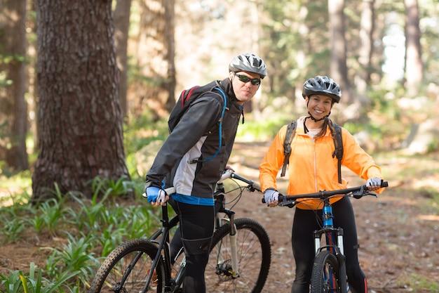 Rowerzysta pary pozycja z rowerem górskim na drodze polnej