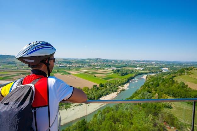 Rowerzysta patrząc na panoramę z regionu winiarskiego langhe