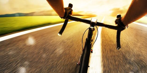 Rowerzysta pedałuje na ulicy w świetle dziennym