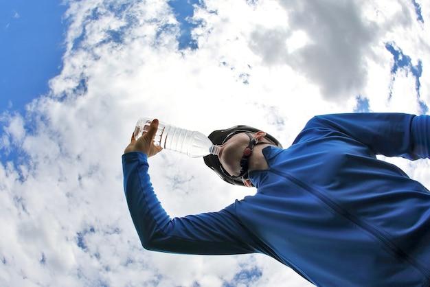 Rowerzysta pije wodę na tle nieba