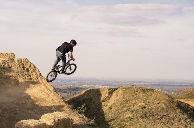 Rowerzysta skaczący i lecący nad wzgórzem
