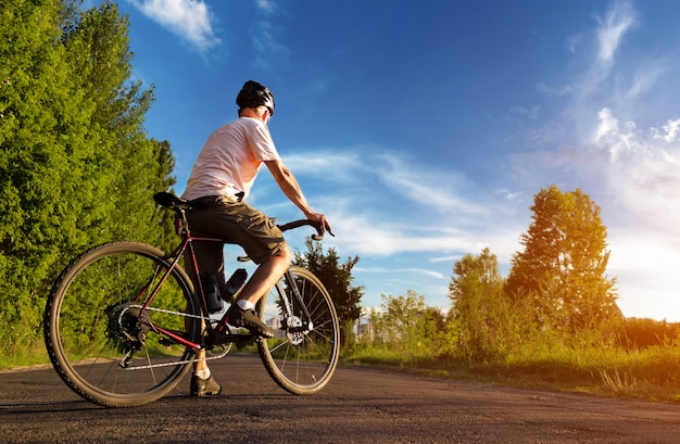Rowerzysta stoi na drodze o zachodzie słońca. piękny krajobraz człowieka z roweru szosowego na tle błękitnego nieba. sportowy styl życia.