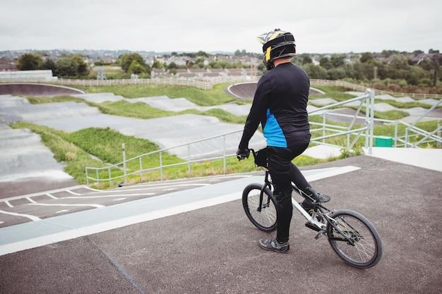 Rowerzysta stojący z rowerem bmx na rampie startowej