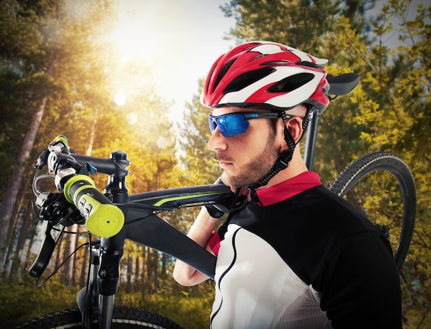 Rowerzysta trzyma na ramieniu swój rower górski