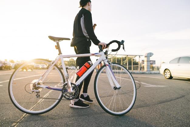 Rowerzysta w czarnej sportowej odzieży jedzie z rowerem.