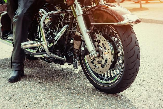 Rowerzysta w czarnych butach siedzi na motocyklu