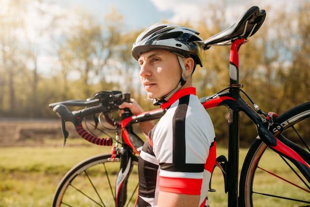 Rowerzysta w kasku i odzieży sportowej trzyma rower na ramieniu, jadąc po asfaltowej drodze.