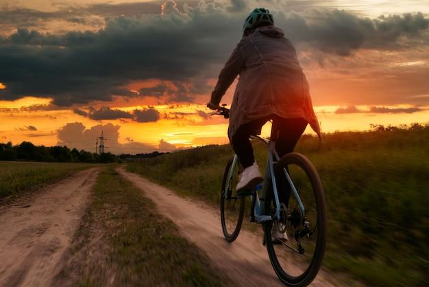 Rowerzysta w kasku jedzie polną ścieżką na tle pięknego nieba o zachodzie słońca