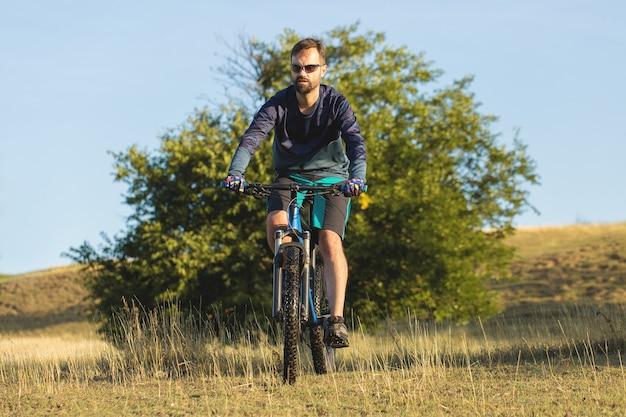 Rowerzysta w krótkich spodenkach i koszulce na nowoczesnym karbonowym hardtailu na tle pola