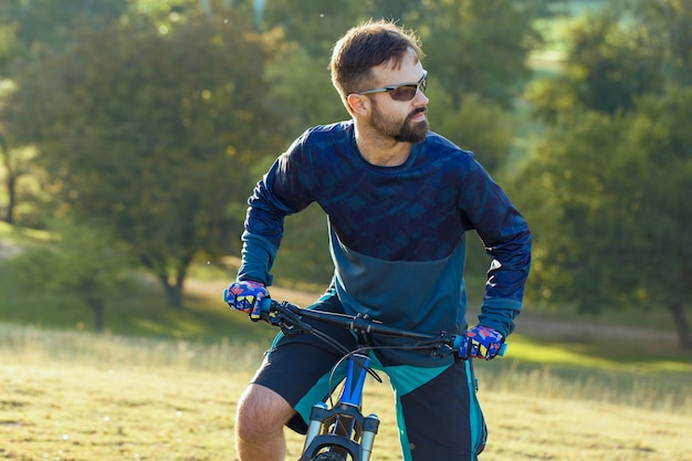 Rowerzysta w krótkich spodenkach i koszulce na nowoczesnym karbonowym rowerze hardtail z widelcem pneumatycznym stojącym na klifie na tle świeżego zielonego wiosennego lasu