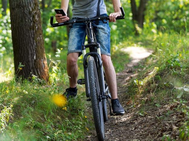 Rowerzysta w lesie na rowerze górskim. zobacz trasę w telefonie