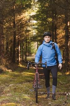 Rowerzysta w niebieskim płaszczu i kasku w parku z wysokimi drzewami