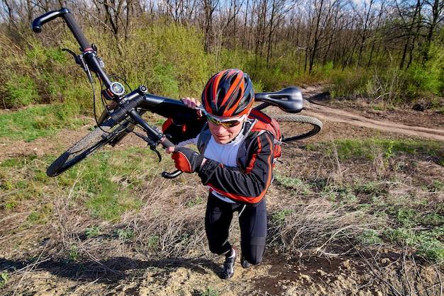 Rowerzysta w odzieży sportowej z rowerem w parku.