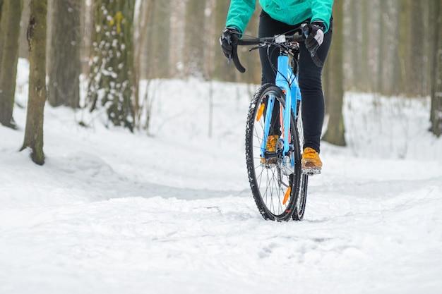 Rowerzysta w śnieżnym lesie