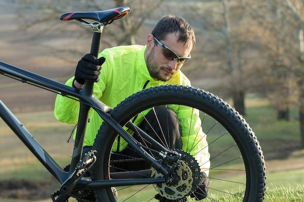 Rowerzysta w spodniach i zielonej kurtce na nowoczesnym rowerze hardtail z włókna węglowego z widelcem pneumatycznym