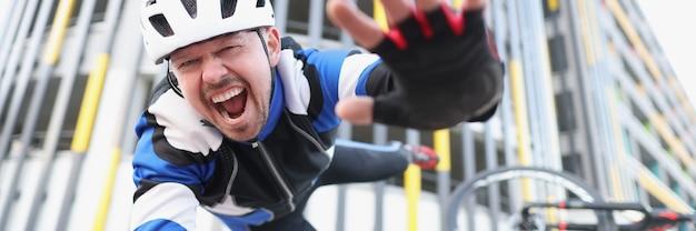 Rowerzysta z krzykiem spada z roweru na asfalt