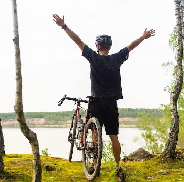 Rowerzysta z podniesionymi rękami w kasku stoi na klifie nad jeziorem.