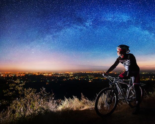 Rowerzysta z rowerem górskim na szczycie wzgórza