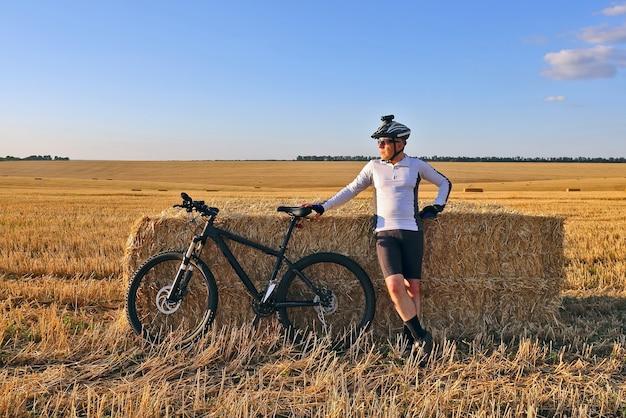 Rowerzysta z rowerem spoczywającym na polu, na którym zbiera się słoma