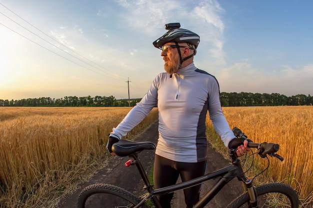 Rowerzysta z rowerem w polu oglądając zachód słońca