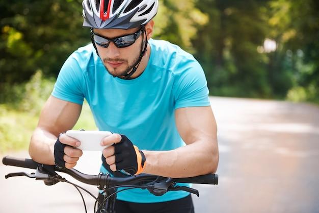 Rowerzysta za pomocą swojego telefonu komórkowego