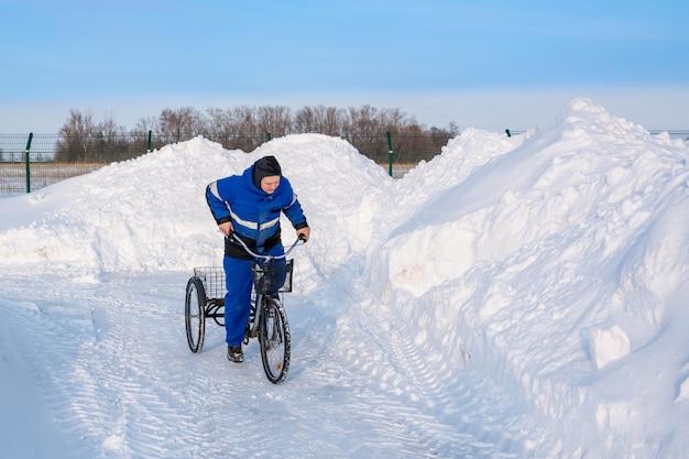 Rowerzysta zimą na trójkołowym rowerze na tle ośnieżonych wzgórz, zasp, ogrodzeń i asfaltu. koła się ślizgają.