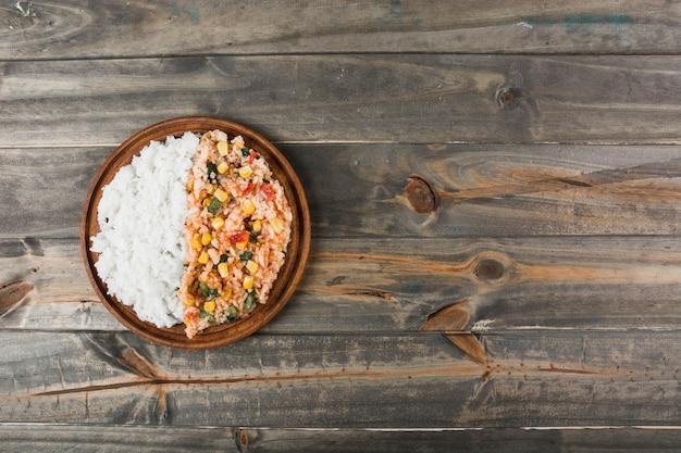 Równina biel i chińczyk smażący ryż na drewnianym talerzu nad stołem
