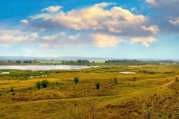 Równina z rzeką i pojedynczymi drzewami pod niebem z malowniczymi chmurami jesienią