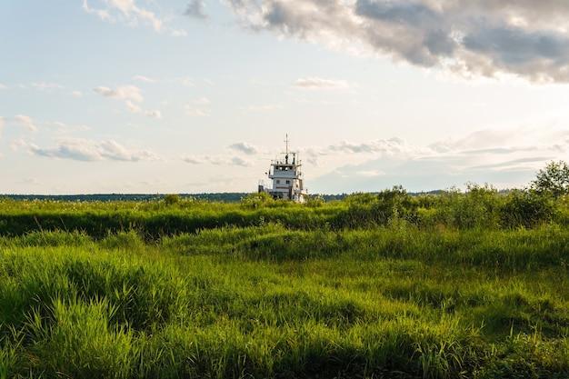 Równina zalewowa w delcie rzeki i nadbudówka holownika widoczna nad trawą