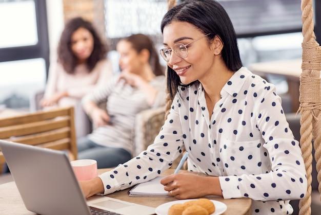 Równowaga finansowa. wesoło pociągająca ładna bizneswoman pisze, uśmiechając się i wpatrując się w ekran