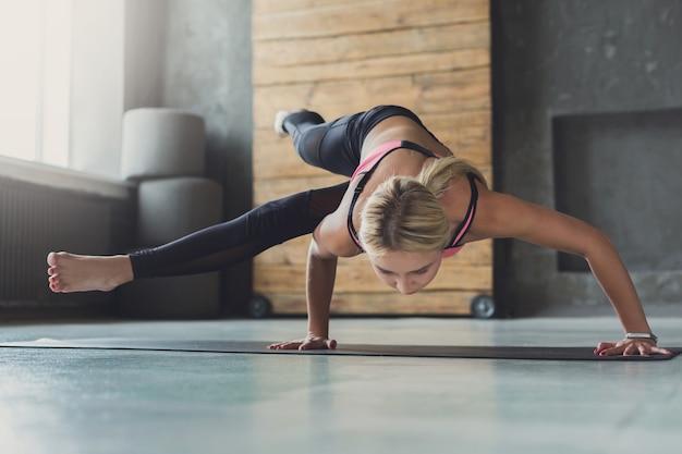 Równowaga podczas stania na rękach. młoda szczupła blond kobieta w zajęciach jogi wykonywanie ćwiczeń asan. zdrowy styl życia w klubie fitness.