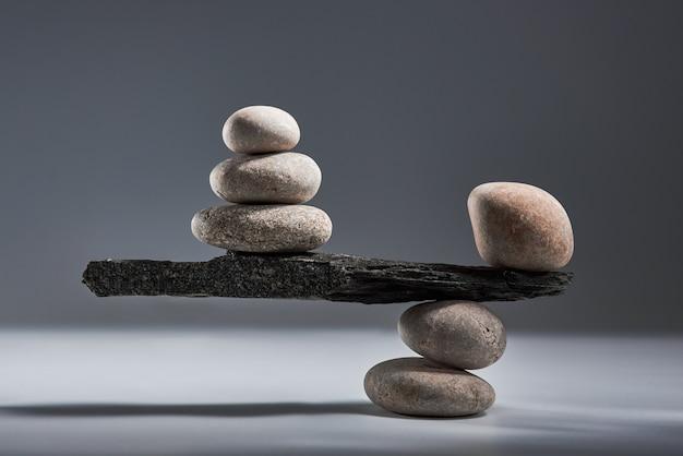 Równoważąca piramida z morskich kamyków na szarym tle to pojęcie harmonii i równowagi