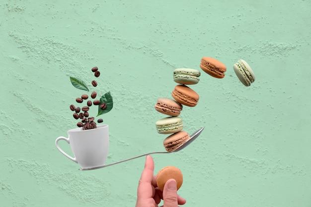 Równoważenie filiżankę kawy i macaronos na palcu