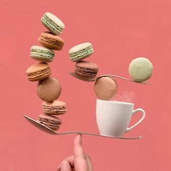 Równoważenie filiżanki kawy i macaronos na palcu