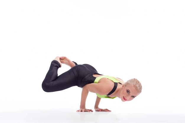 Równoważenie jogi. ujęcie wesołej młodej kobiety uśmiechającej się do kamery ćwiczącej jogę robiącej pozycję stojącą na rękach na białym tle copyspace zdrowie witalność szczęście uroda koncepcja ciała