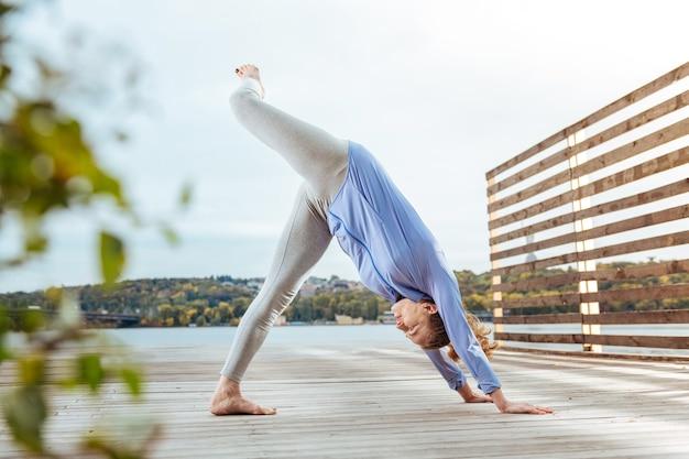 Równoważenie kobieta balansująca w skomplikowanej pozie jogi podczas ćwiczeń na świeżym powietrzu