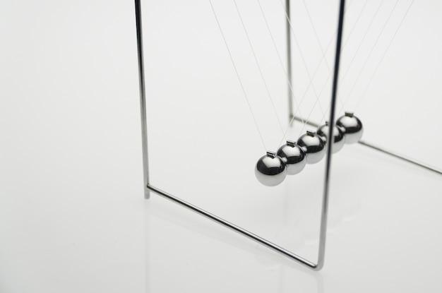 Równoważenie kulki na białym tle, na białym tle. pomysł na biznes. kołyska newtona